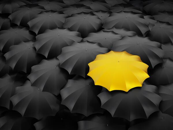 One yellow umbrella in a sea of black umbrellas, suggesting creativity.
