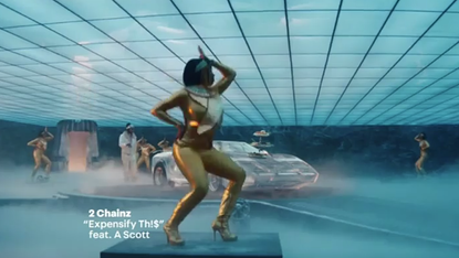 2 Chainz Girls in gold outfits on pedestals dance around fancy car.