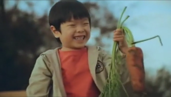 Boy with carrot that he planted himself