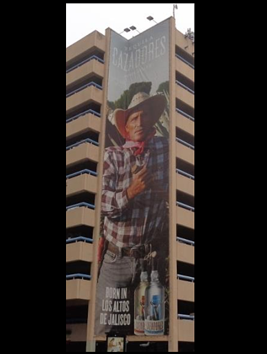 Tequila Cazadores building banner promoting drinking.