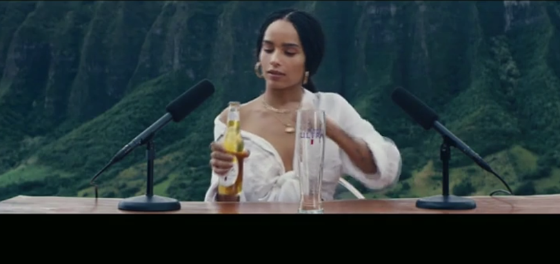 Zoe Kravitz sits at a desk in the mountains with two microphones doing an 'experience' with Michelob Ultra Pure Gold.