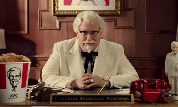 Colonel Sanders sitting at a desk